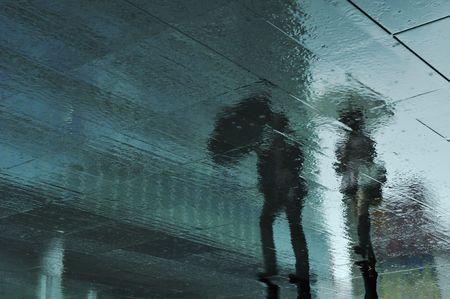 regenachtige stoep reflectie van wandelen paar in Tokio, Japan tijdens het regenseizoen, die meestal enige tijd in beslag neemt in juni
