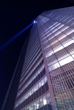 giant glass wall of modern skyscraper building on night sky background with blue light projector on the top Stock Photo - 3363575