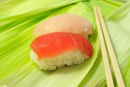 close up traditional fresh japanese sushi on green leafs with wooden chopsticks, focus on front piece Stock Photo - 3447645