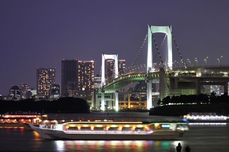 very famous Tokyo landmark, Tokyo Rainbow bridge over bay waters with scenic night illumination and traditional japanese boats Stock Photo