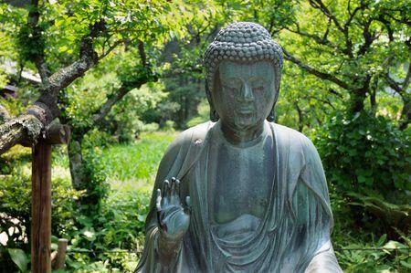 stone buddha: japanese Buddha statue in zen garden environment in Kamakura, Japan; focus on face and hand
