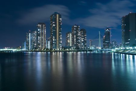 waters: modern Tsukuda district of Tokyo at night over waters of Sumida River Stock Photo