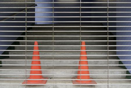 entrance stairs closed with metallic rolls and two red plastic cones photo