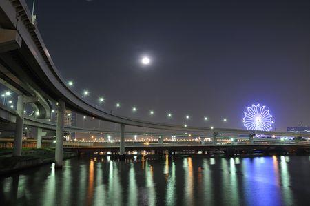 ferriswheel:  autostrada impiccati di accesso stradale sulla baia di Tokyo acque in fase di notte con la luna e ferris wheel illuminazione su indietro
