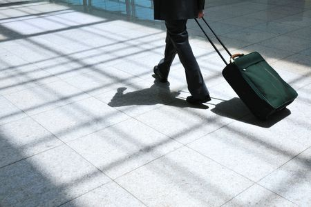 businessman carry the suitcase  and go forward by light pavement pathway in modern airport environment