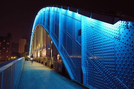pedestrian way along the metallic arc structure of Eitai bridge with moving bicycle by night time in Tokyo Japan; focus on metallic structure Stok Fotoğraf