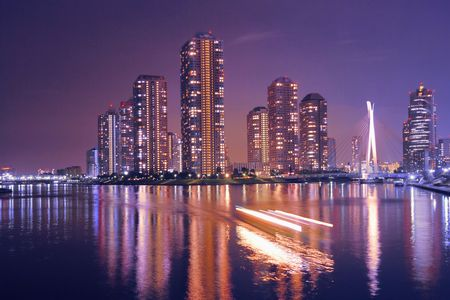 modern Tokyo buildings with night reflection in water and light traces of moving ship, Japan