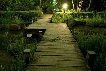 source d eau: Pont de bois dans un jardin japonais nuit