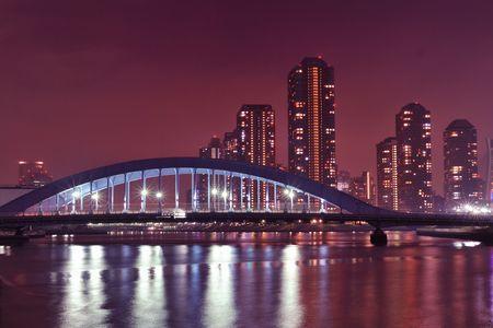 Tokyo skyline view over Sumida river night waters with metallic Eitai bridge and Tsukishima residential district