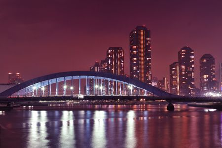 Tokyo skyline view over Sumida river night waters with metallic Eitai bridge and Tsukishima residential district