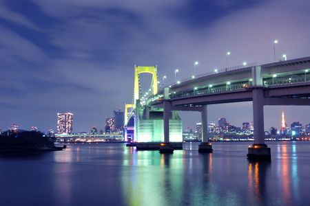 one of famous Tokyo landmarks, Tokyo Rainbow suspension bridge supports over night waters with scenic colourful illumination Stock Photo