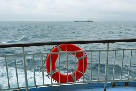 handrails: red life-buoy on the ships handrails with stormy sea backward; focus on handrails and buoy Stock Photo