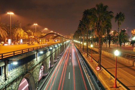 scenic night view to the famous Passeg de Colom street close to Barcelona port area; sharp focus on foreground wall and right light  photo