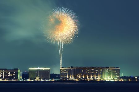 night city skyline over sea waters with firework over buildings Фото со стока