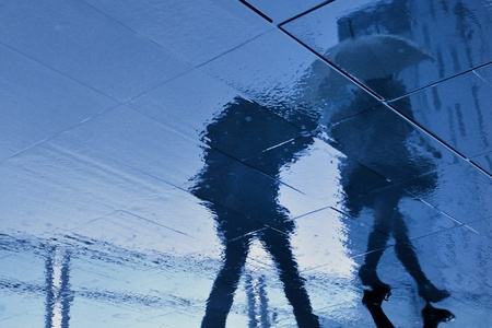 rainy pavement reflection of walking couple in Tokyo, Japan during rainy season which usually takes time in June Archivio Fotografico