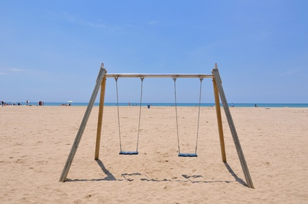 double beach swing over sand and blue sky background, Spain photo
