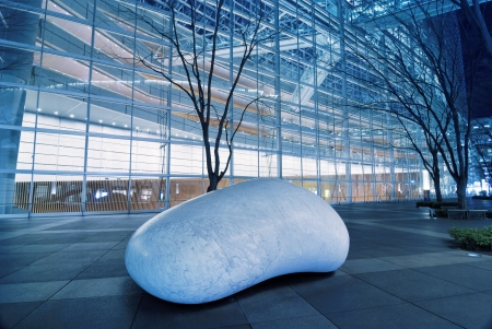TOKYO, JAPAN -January 23, 2008 : white marble stone sculpture ISHINKI by Kan Yasuda inside futuristic environment of Tokyo International Forum by night Redactioneel