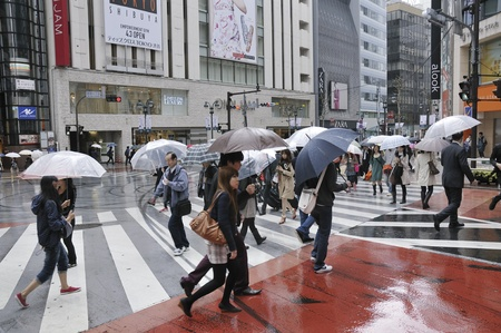 rain japan: TOKYO, JAPAN -APRIL 23, 2011 : people cross over street in Tokyo Shibuya area under rain. Shibuya district is very famous for its fashion shops and crowds of young people. Editorial