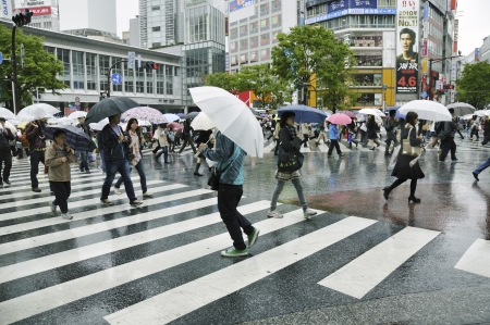 TOKYO, JAPAN -APRIL 23, 2011 : people cross over famous Tokyo Shibuya crossing under rain. Shibuya crossing is known as biggest and most crowded in the world. Editoriali
