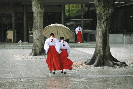 Japanese temple yard with girls in traditional clothing walking under heavy rain Stock Photo