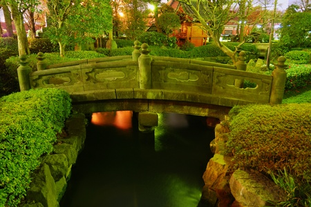 bridge over water:  Japanese garden by night with traditional bridge over water pond at Asakusa, Tokyo, Japan