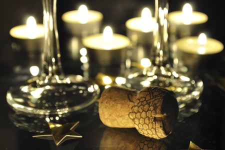 holiday still-life with Champagne cork , two glasses and many candles behind; focus on foreground cork photo