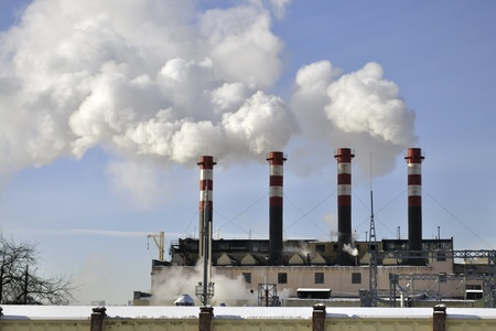 power station chimneys over blue sky background photo