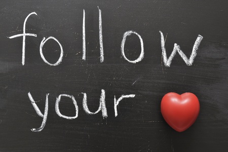 hand written follow your with red heart symbol on black chalkboard photo