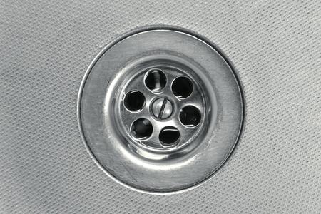metallic water drain close-up; focus on drain holes photo