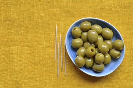 pitted: snocciolate le olive verdi sul piatto blu oltre tovaglia gialla