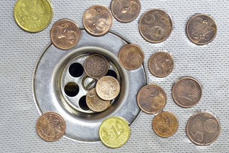 cast off: small Euro coins are cast-off and go to drain