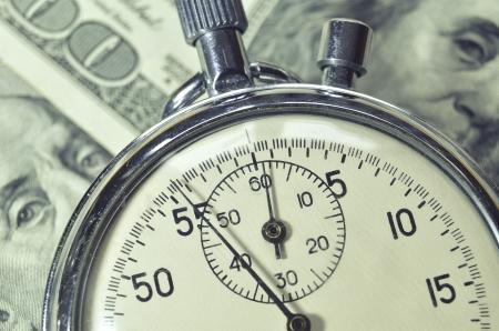 cash money: cron�metro se pone sobre los billetes de d�lar de Estados Unidos, se centran en la flecha reloj
