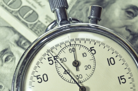 stopwatch lays over US dollar banknotes; focus on watch arrow