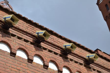 line of surveillance cameras on the old building wall photo