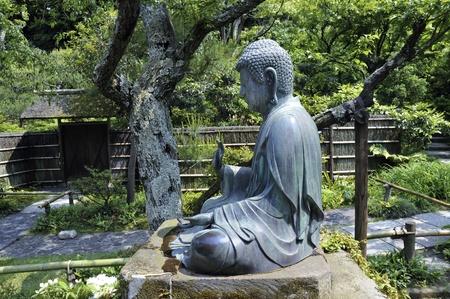 Japanese Buddha Statue In Zen Garden Environment In Kamakura, Japan Photo
