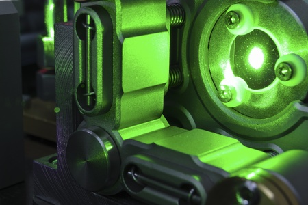 mirror reflection of powerful green laser light inside scientific system Stockfoto