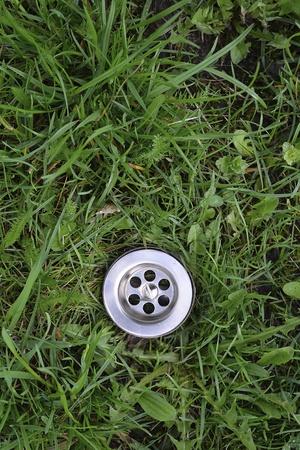 sink hole: metallic sink hole among green grass background