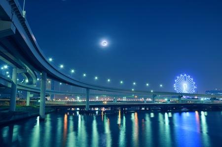ferriswheel: impiccato-up sulla strada strada acque della baia di Tokyo durante la notte con la luna e ferris-wheel illuminazione su indietro Archivio Fotografico