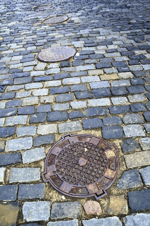 scenic old-time cobblestone city pavement in twilight light with many manholes Stock Photo - 13486084