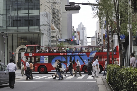 Tokyo, Japan - September 27, 2008: Red cruise bus in famous Ginza district. Cruise bus is popular tourists attraction to enjoy the Tokyo  sightseeing in short trip. Редакционное