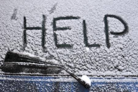 Help woord geschreven op de achterkant autoruit gedekt door hevige sneeuwval Stockfoto