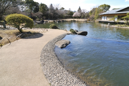 tea house: scenic Japanese pond with stone pathway and tea house on opposite side; focus  on foreground
