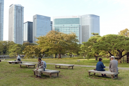 Tokyo, Japan - November 2, 2007 : people take a rest at the place of famous Hamarikyu gardens in Tokyo Chuo Ward. Hamarikyu zen gardens were built originally as duck hunting place of Shogun Tokugawa family in the 17th century.