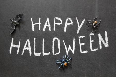 halloween message: Happy Halloween message handwritten on blackboard with spiders around Stock Photo