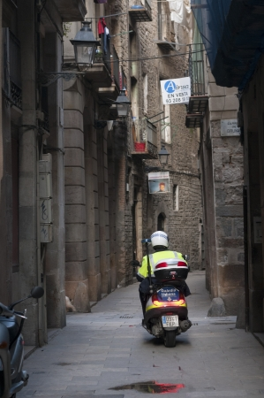 patrolling: Barcelona, Spain - November 16, 2009 : policemen on motorcycle patrolling the narrow street of famous Gothic Quarter (Barri Gotic) by early morning.