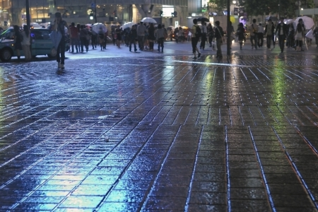 rain japan: rainy pavement reflection by  night with crowd apart in Tokyo Metropolis, focus on pavement Stock Photo