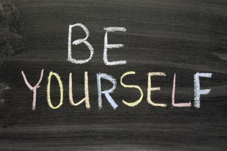 phrase: be yourself phrase handwritten on school blackboard