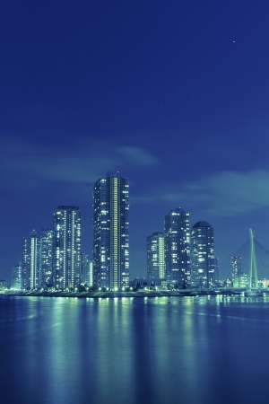 blue toned cityscape of night Tokyo, modern buildings at Tsukishima district with reflection in Sumida river photo
