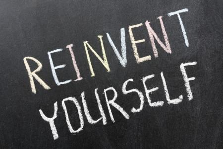 phrase: reinvent yourself phrase handwritten on school blackboard Stock Photo