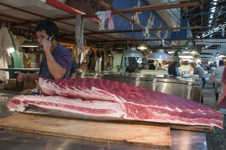 Tokyo, Japan - September 27, 2008: salesman talks by phone behind the big raw tuna body laying on the table top on the world famous Tokyo Tsukiji fish market.